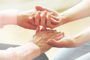 caretaker holding the hands of a elderly woman