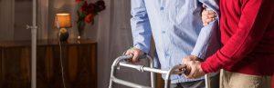 Older man walking with walker in caregiver's assistance