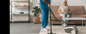 woman smiling as caretaker vacuums her home