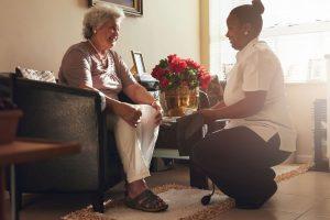 caretaker taking blood pressure for elderly woman