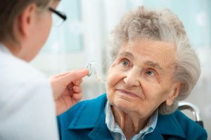 elderly woman with hearing doctor looking at hearing aids