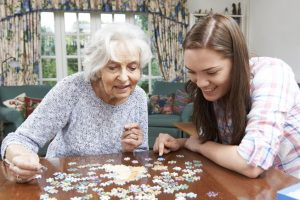 woman and caregiver doing a puzzle